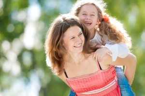 14858700 - beautiful and happy young mother giving piggyback ride to her laughing daughter